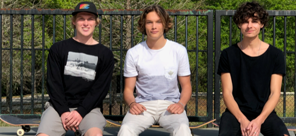 Three young boys sitting with skateboards
