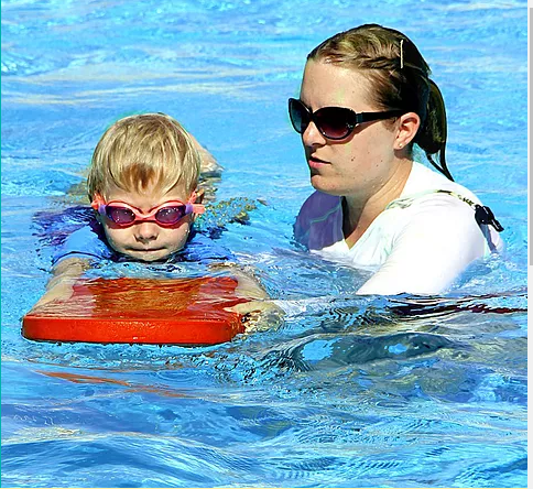 Child on paddleboard during swimming lessons